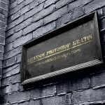 señalética mockup template de placa de madera negra con nombre de la calle o avenida en letras doradas sobre pared de ladrillo. Aspecto clásico retro